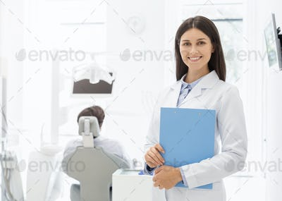 Attractive young dentist smiling at camera over dental office background