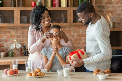 Lovely parents giving their daughter gift during breakfast