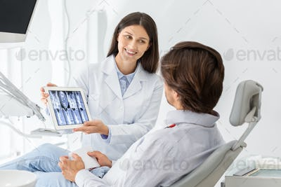 Beautiful dentist showing his patient x-ray results on digital tablet