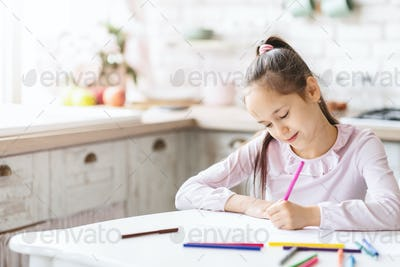 Cute little girl sitting in kitchen and drawing