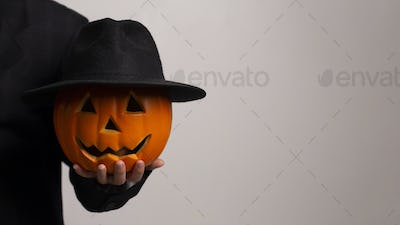 Cut out pumpkin face put on black hat and looking seriously