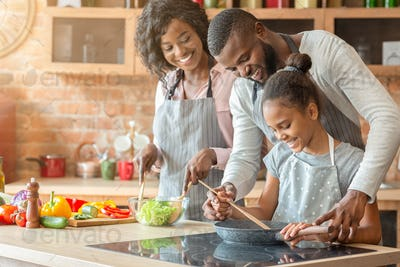 Afro parents teaching their daughter how to cook