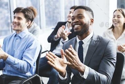 Happy businessmen applauding good presentation in office