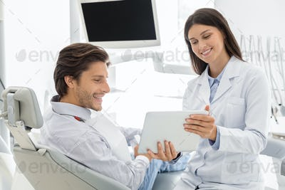 Cheerful dentist showing patient results of treatment on digital tablet