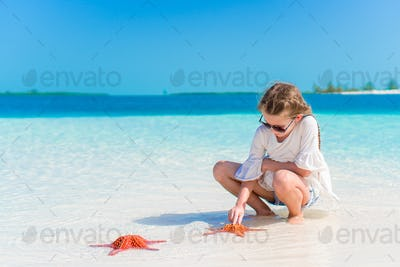 Adorable little girl with starfish on white beach