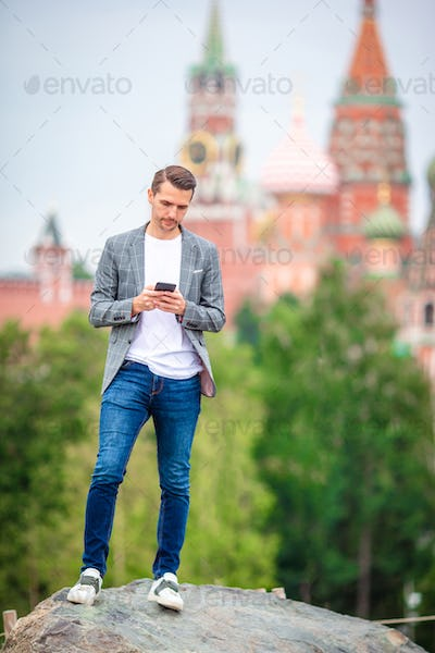 Happy young urban man drinking coffee in european city