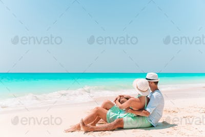 Young couple walking on tropical beach with white sand and turquoise ocean water at Antigua island