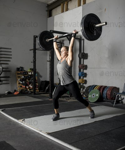 Strong femal weight lifter with heavy weights over her head, two thirds profile shot.