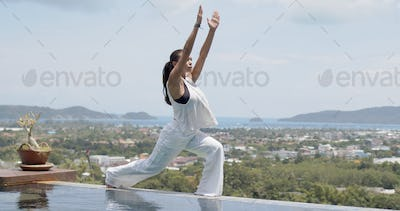 Adult woman doing balancing exercise poolside against amazing landscape of resort on sea shore