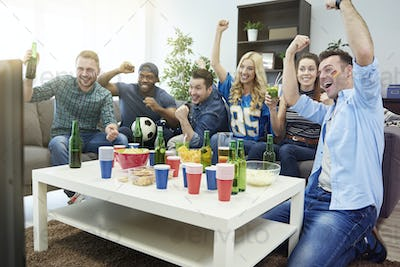 Excited group of friends watching sport on tv