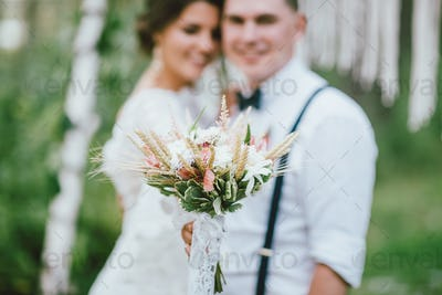 Beautiful smiling bride brunette young woman in the white lace dress with wedding boho bouquet
