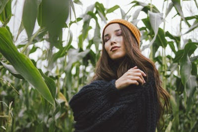 Beautiful carefree long hair asian girl in the yellow hat and knitted sweater in autumn corn field