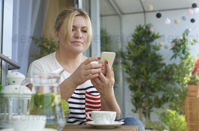 Woman using mobile phone on the balcony