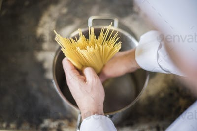 Chef inserting pasta to the kitchen pot