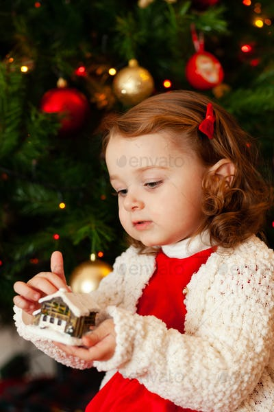 Beautiful little child near Christmas tree.