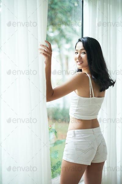 Playful ethnic woman near window