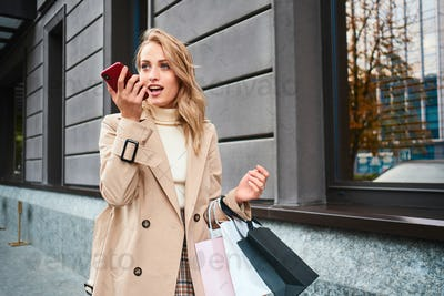 Stylish blond girl in beige coat with shopping bags recording voice messages on cellphone on street