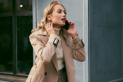 Pretty casual blond girl in trench coat emotionally talking on cellphone outdoor