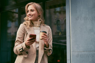 Attractive smiling blond girl in trench coat with coffee and cellphone joyfully looking away outdoor