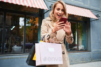 Excited blond girl in stylish trench coat with shopping bags joyfully using cellphone on city street