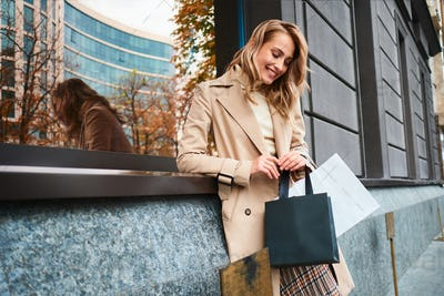 Portrait of pretty joyful blond girl in beige coat with shopping bags on city street