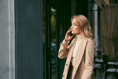 Side view of attractive blond girl in trench coat thoughtfully talking on cellphone outdoor