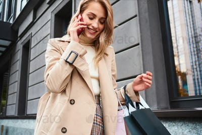 Pretty stylish blond girl in beige coat with shopping bags happily talking on cellphone on street