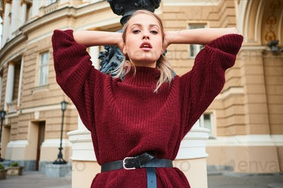 Portrait of attractive stylish blond girl in knitted sweater sensually looking in camera outdoor