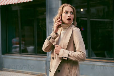 Attractive casual blond girl in trench coat talking on cellphone dreamily looking away outdoor