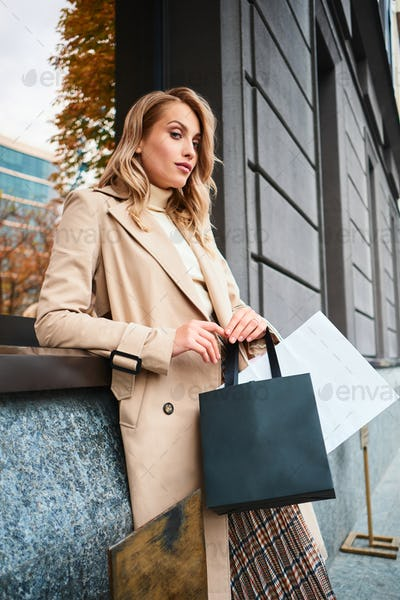 Stylish blond girl in trench coat with shopping bags confidently looking in camera on street