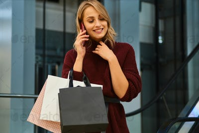 Pretty smiling blond girl in knitted sweater happily talking on cellphone in shopping mall
