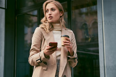 Attractive casual blond girl in trench coat with coffee to go and cellphone outdoor