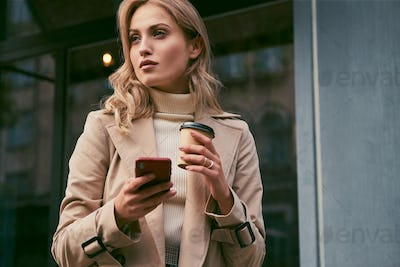 Beautiful girl in trench coat with coffee to go and cellphone thoughtfully looking away outdoor