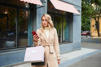 Beautiful casual blond girl in stylish trench coat with shopping bags using cellphone on city street