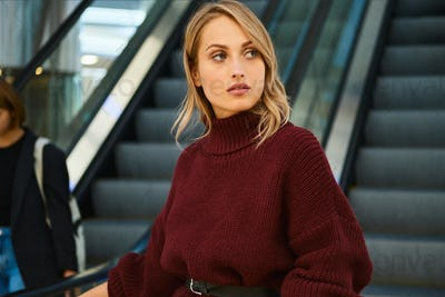 Beautiful blond girl in knitted sweater confidently looking away on escalator in shopping mall