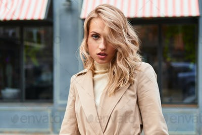 Attractive sexy blond girl in stylish trench coat sensually looking in camera on city street