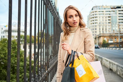 Blond girl in stylish trench coat with shopping bags dreamily looking in camera on city bridge