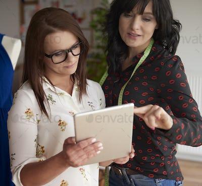 Two fashion designers using digital tablet