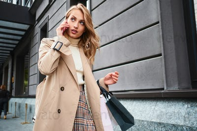 Stylish blond girl in coat with shopping bags talking on cellphone looking away on street