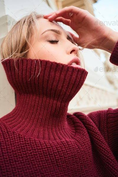 Close up beautiful blond girl in knitted sweater sensually posing outdoor