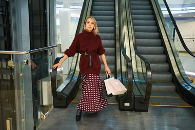 Attractive stylish blond girl with shopping bags on escalator in modern shopping mall