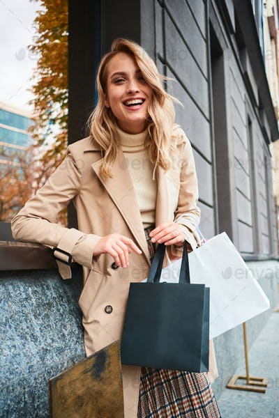 Pretty cheerful stylish blond girl in beige coat with shopping bags happily laughing on street
