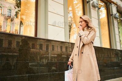 Stylish blond girl in beige coat with shopping bags dreamily looking at store window on city street