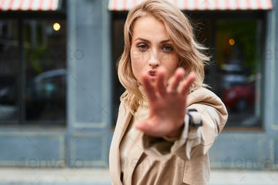 Beautiful sensual blond girl in stylish trench coat pulling hand in camera on city street