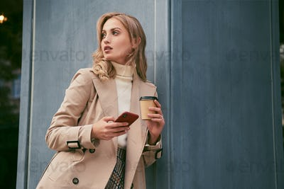 Attractive blond girl in trench coat with coffee to go and cellphone thoughtfully standing outdoor