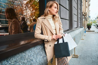 Side view of stylish blond girl in beige coat with shopping bags looking away on city street