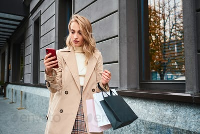 Beautiful stylish blond girl in beige coat with shopping bags using cellphone on street