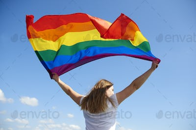 Rear view of young woman waving rainbow flag