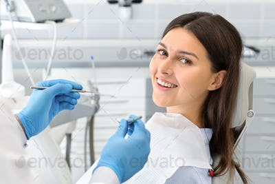 Portrait of young happy lady sitting in dentist chair