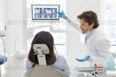 Dentist doctor explaining his patient x-ray results